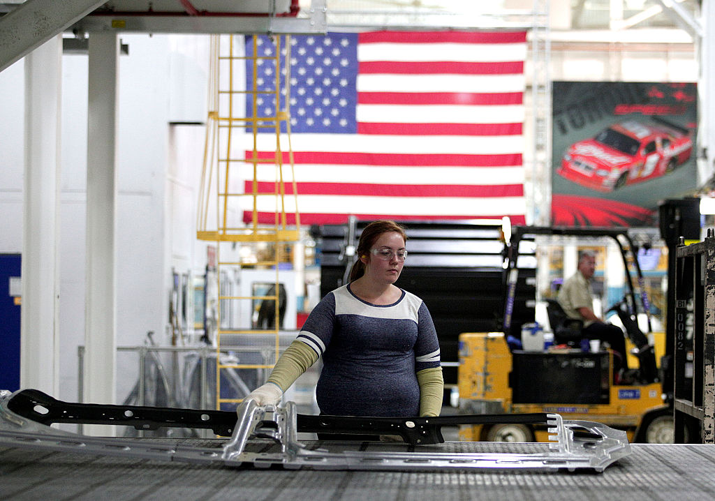 A worker handles parts for Fiat Chrysler Automobiles as they come off the press