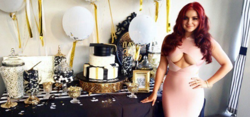 Ariel Winter stands in front of a graduation cake and table in a cut out dress.