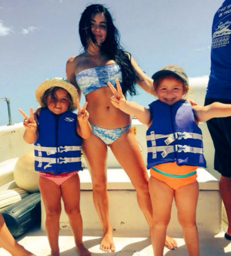 Ariel Winter poses in a blue bikini on a boat with her two nieces.