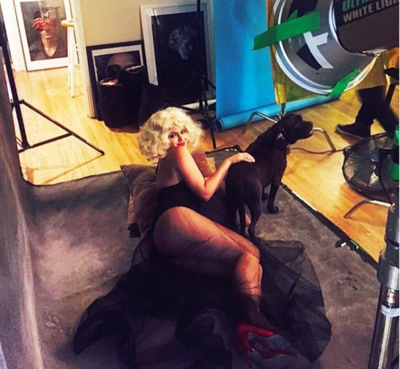 Ariel Winter poses on the ground in a black dress and blonde wig while petting a black dog.