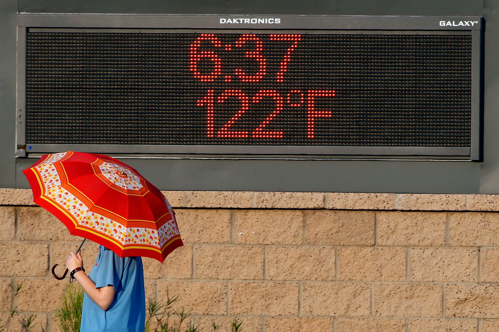 sign saying 122 degrees Fahrenheit and person holding umbrella to protect from sun in Phoenix