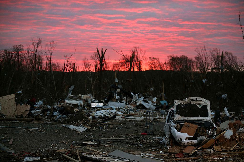 The sun rises behind debris that was left when a tornado hit Arkansas