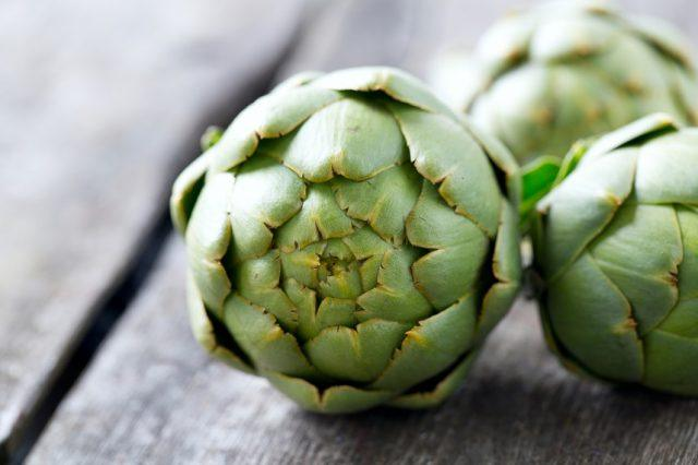 Fresh artichokes on a wooden table.
