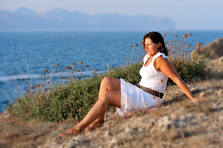 Beautiful mature woman sitting alone on the beach