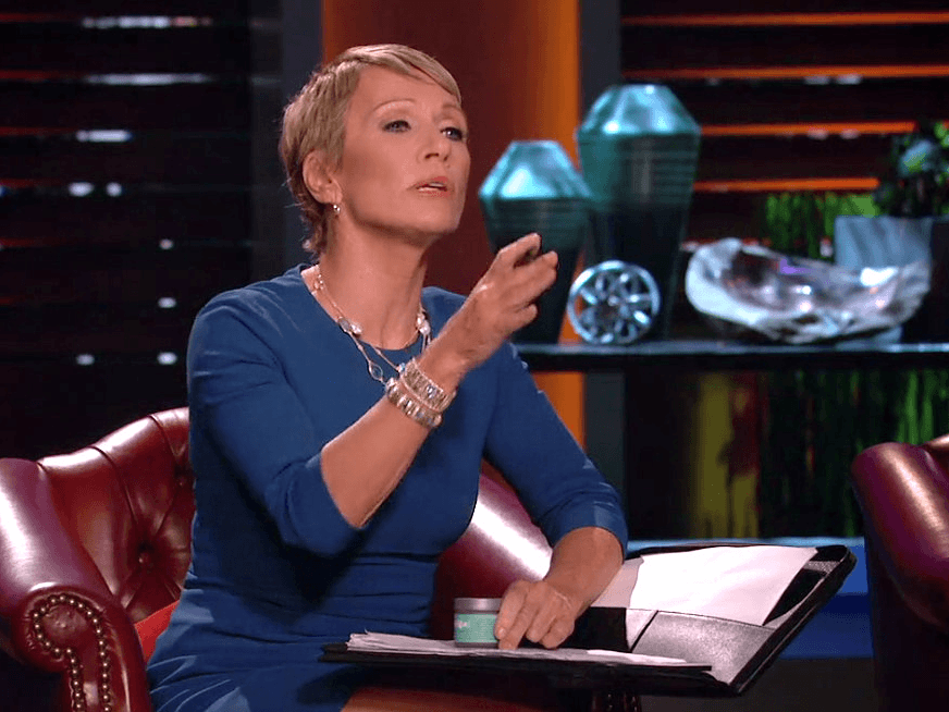 Barbara Corcoran gestures while holding a pen and a notebook on her lap in Shark Tank