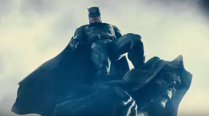 Batman towers in the sky while wearing his suit