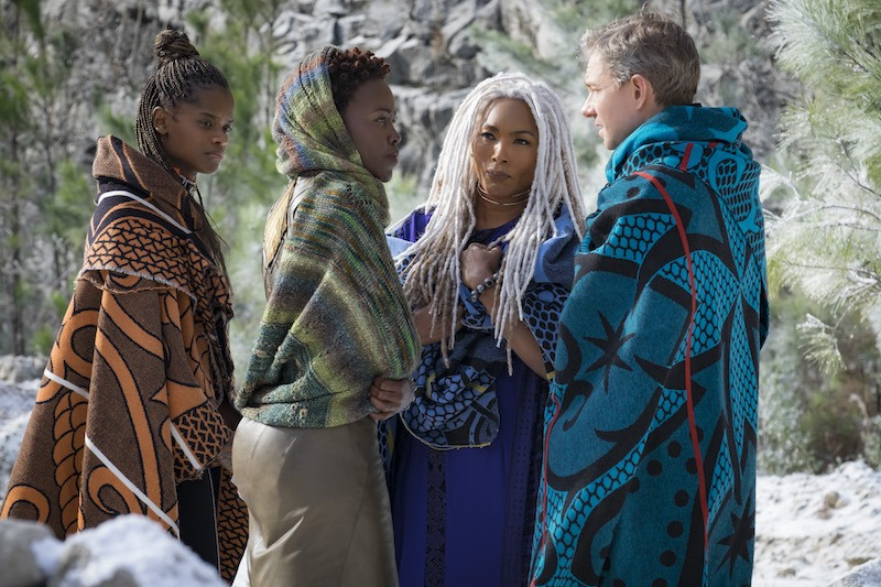 A trio of women in shawls talk with a man in Black Panther