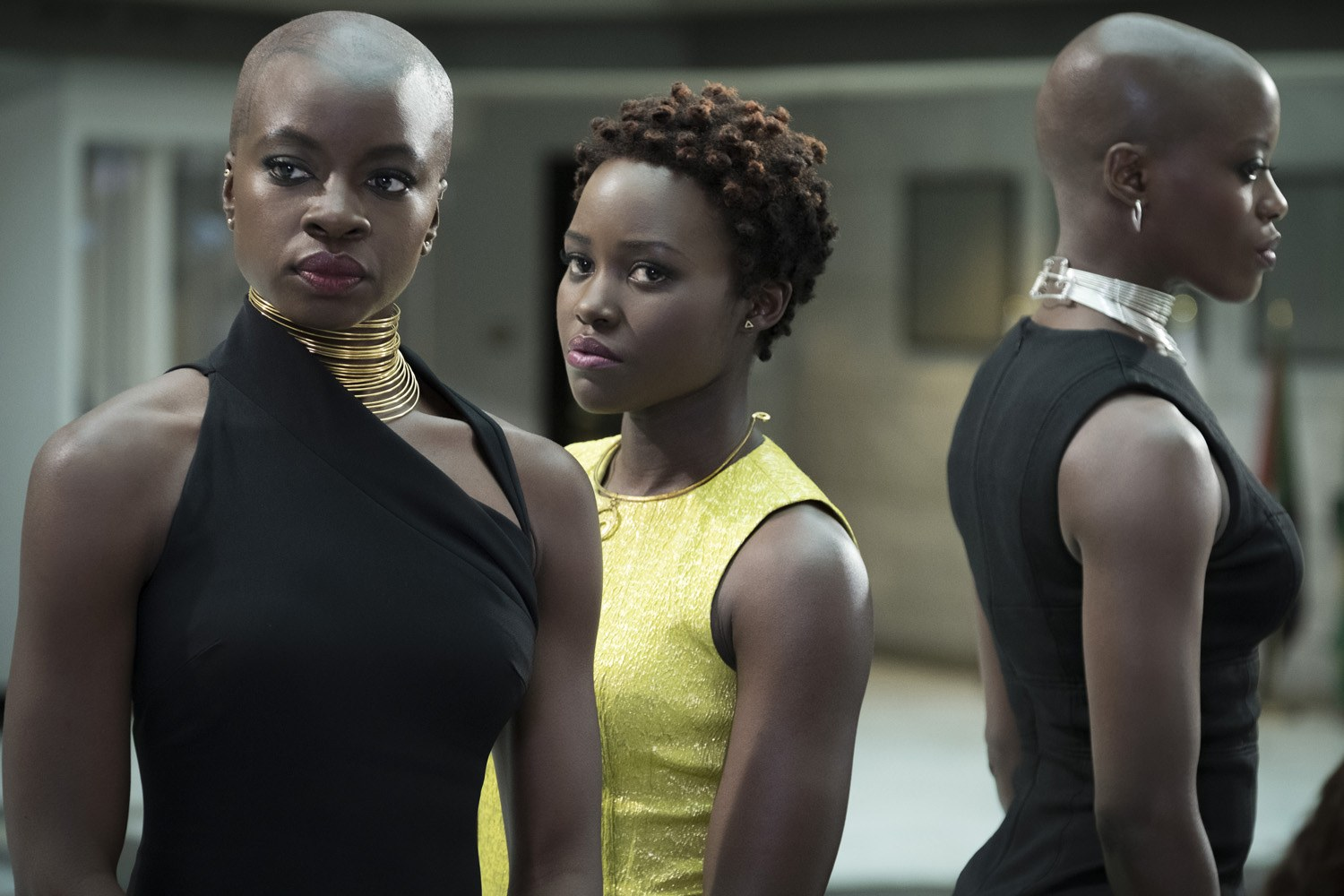 Danai Gurira's Okoye, Lupita Nyong'o's Nakia and Florence Kasumba's Ayo stand next to each other in dresses in <em>Black Panther</em