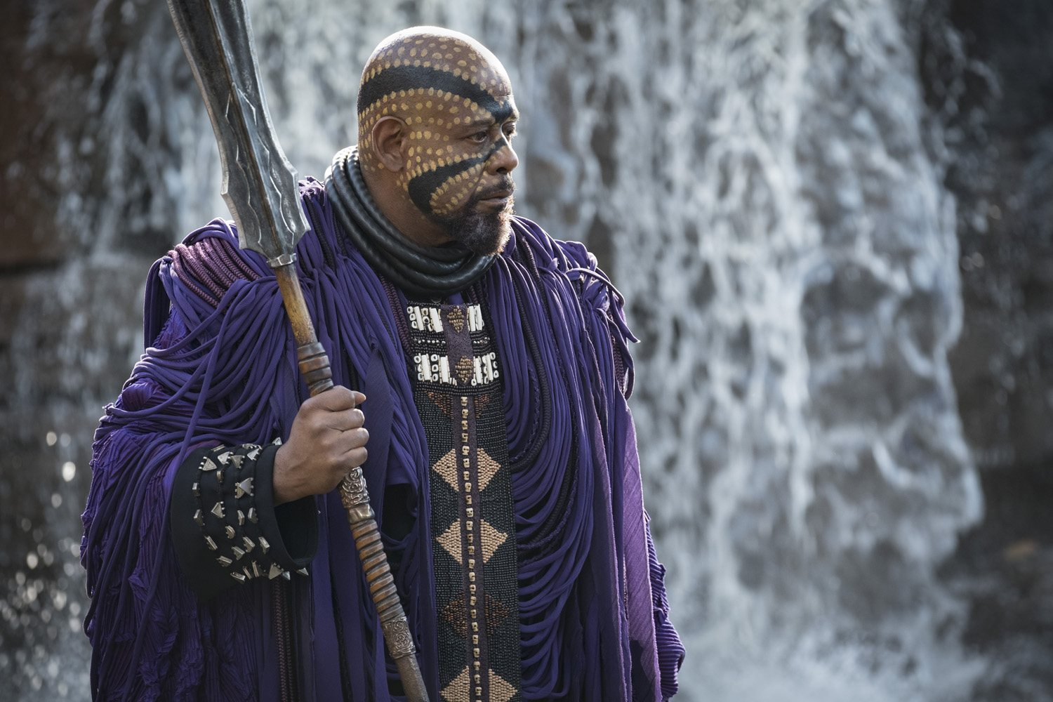 Forest Whitaker's Zuri wears purple garb and elaborate face paint while holding a giant scepter in Black Panther