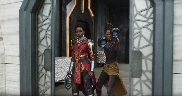 Lupita Nyong's Nakia stands to the left of Letita Wright's Sure while holding weapons in Black Panther.