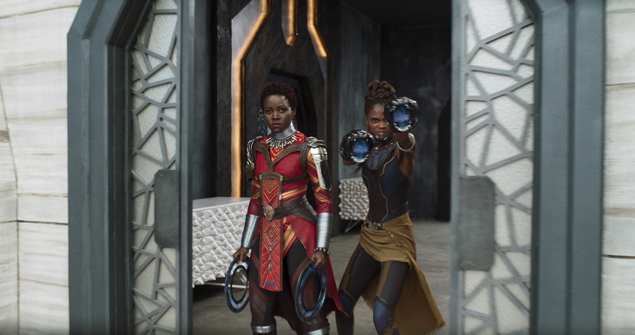 Lupita Nyong's Nakia stands to the left of Letita Wright's Shuria while holding weapons in Black Panther