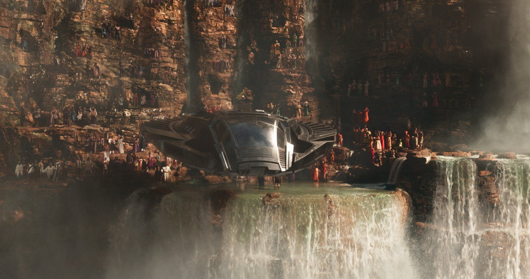 Many people gathered alongside a waterfall as a spacecraft hovers