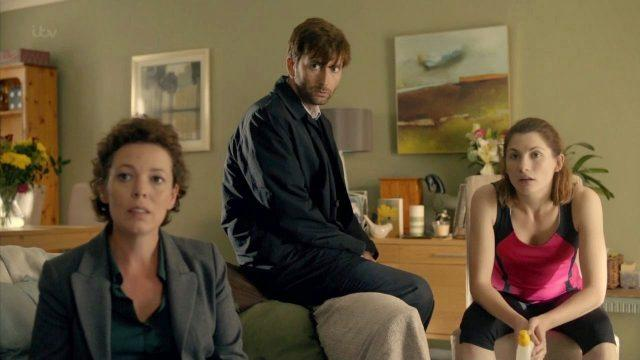 Actors Olivia Colman, David Tennant and Jodie Whittaker sit in a living room in a scene from the ITV series 'Broadchurch.'