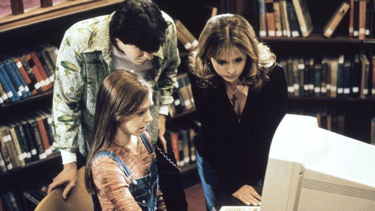 Xander and Buffy look over Willow's shoulder as she works on a computer in the library