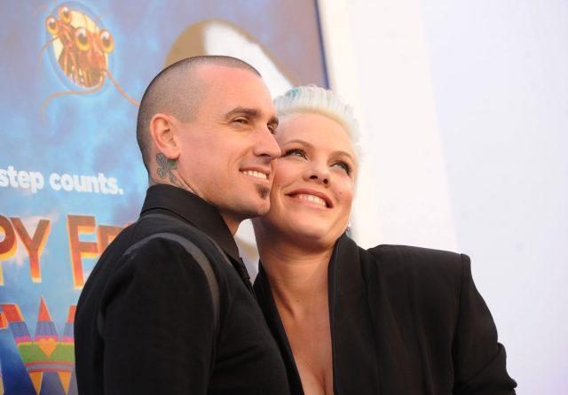 Athlete Carey Hart and singer Pink stand close together and smile for cameras