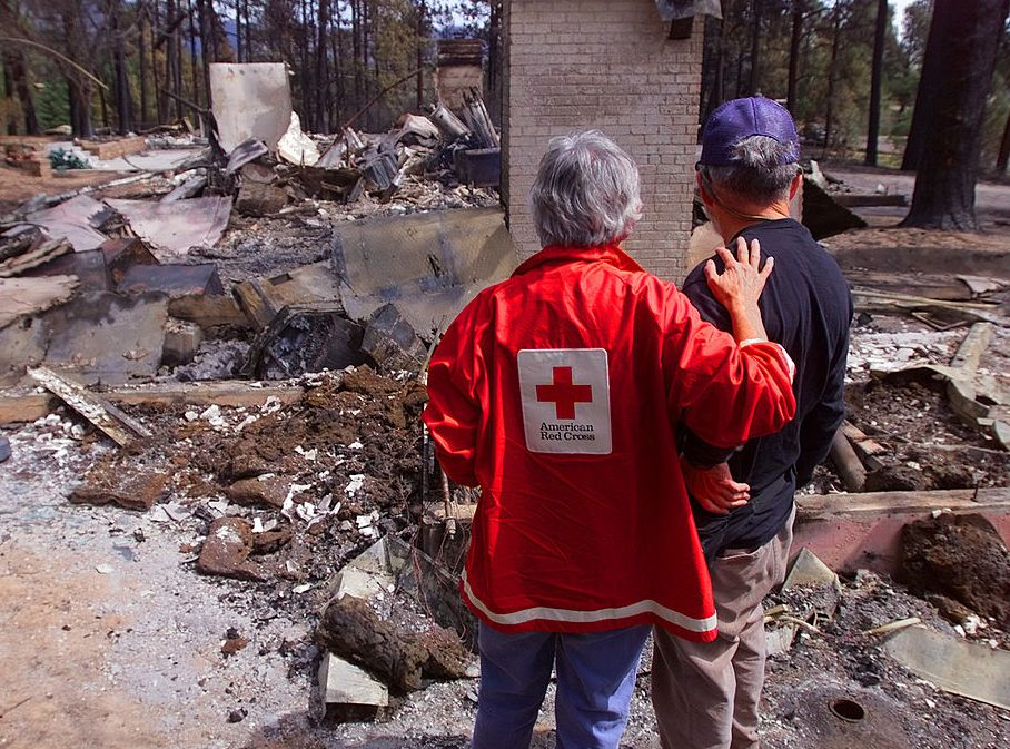 red cross volunteer comforts fire victim