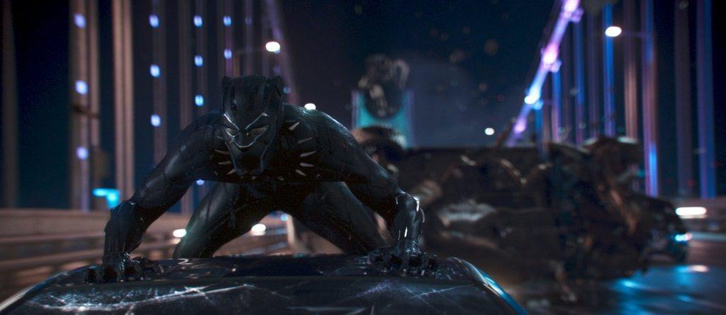 Chadwick Boseman in Black Panther wearing his suit while perched on a moving car