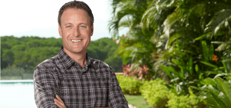 Chris Harrison is smiling with his arms crossed.