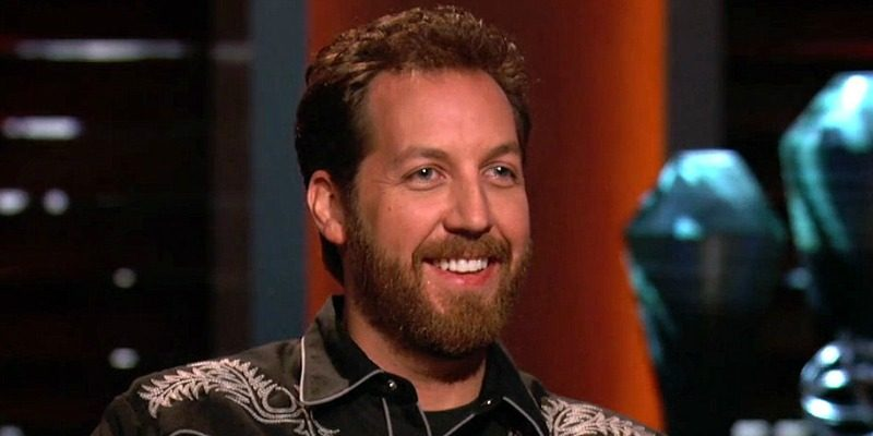 Chris Sacca is smiling as he sits on the set of Shark Tank.