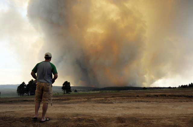 A man watches an approaching fire.