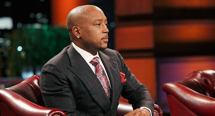 Daymond John sits in a leather chair on Shark Tank