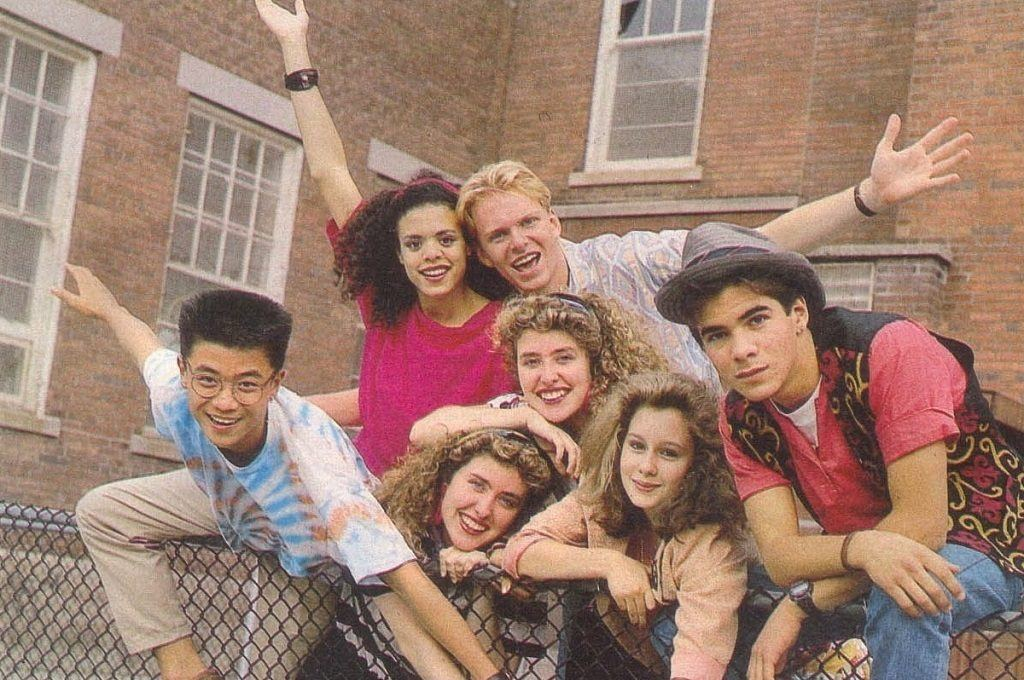 A group of preteens leaning on a fence with their arms out in front of a school building