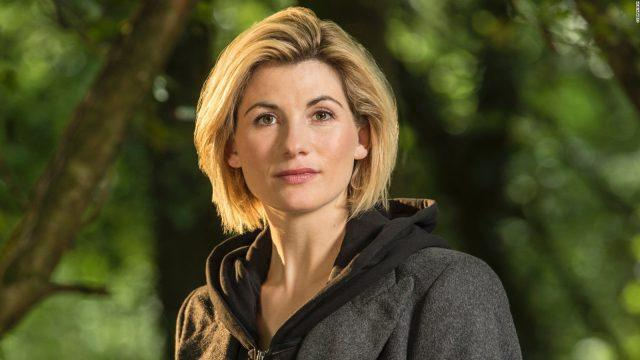 Jodie Whittaker stands in front of trees n a grey sweatshirt in a promotional photo for 'Doctor Who.'