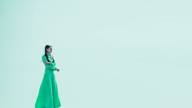 woman in a green dress on a green background