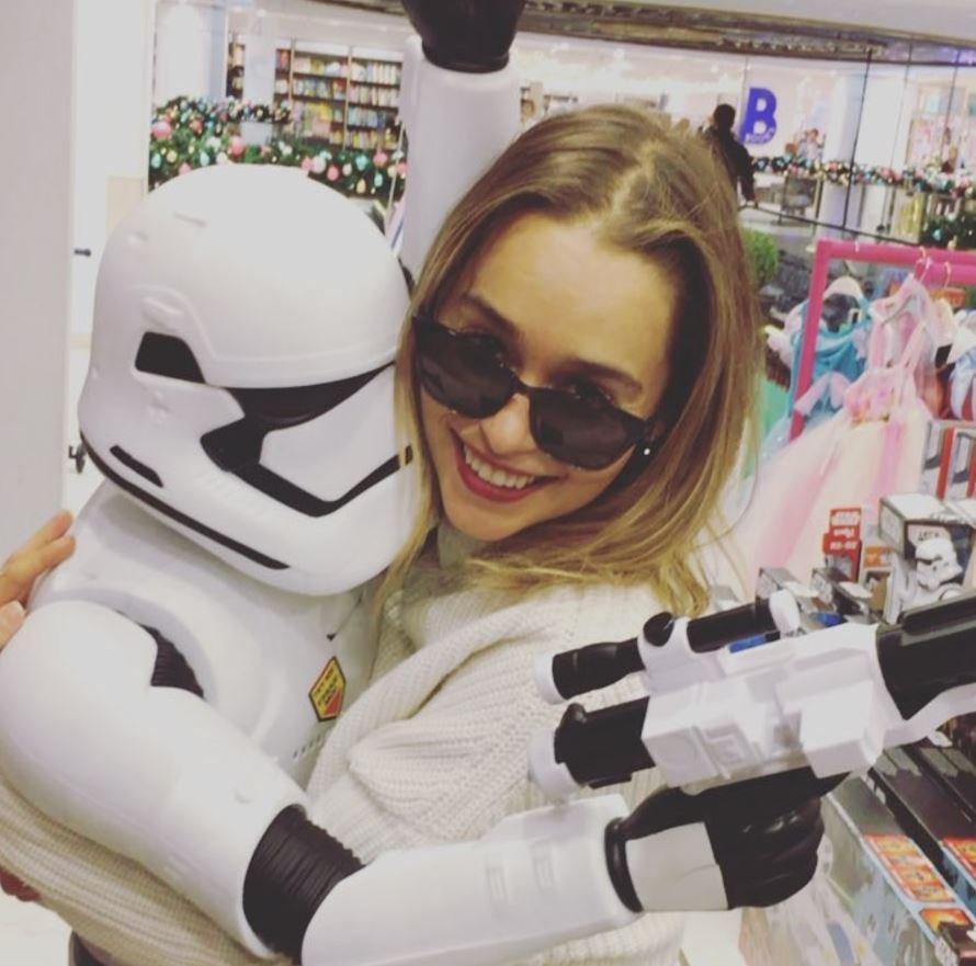 Emilia Clarke smiling and hugging a Stormtrooper