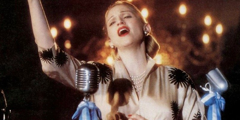 Madonna is singing at a microphone in Evita.