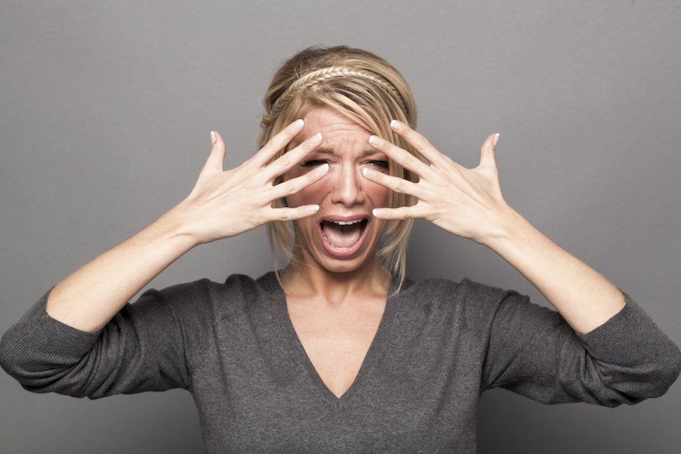 blond girl complaining with tears and hands hiding her face