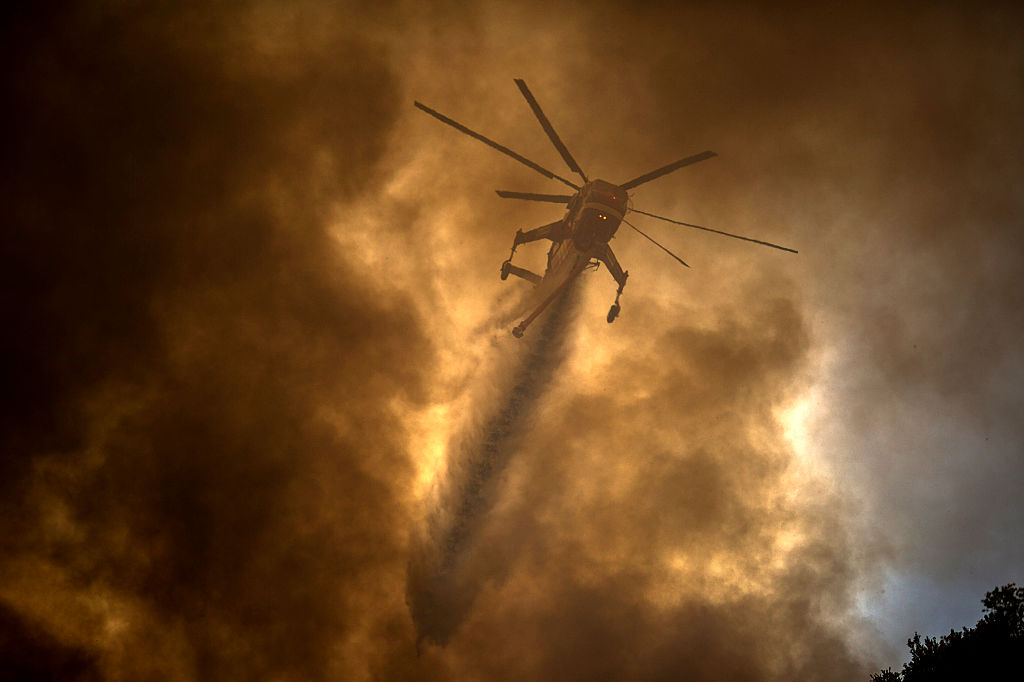 a helicopter making a drop during a wildfire