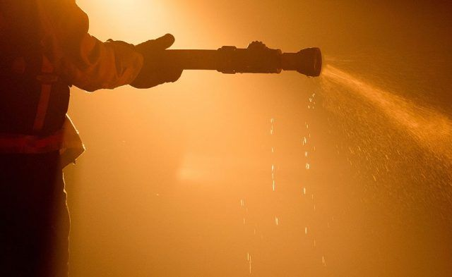 A firefighter with a water-filled hose.
