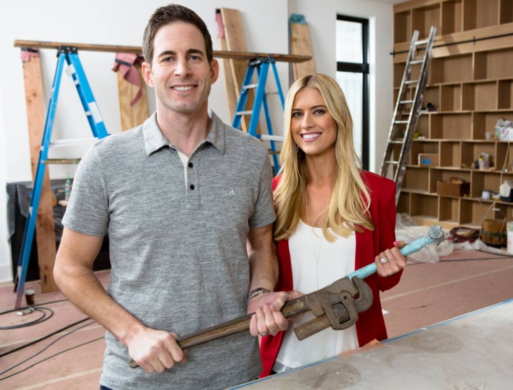 Tarek and Christina El Moussa hold tools in a house undergoing construction