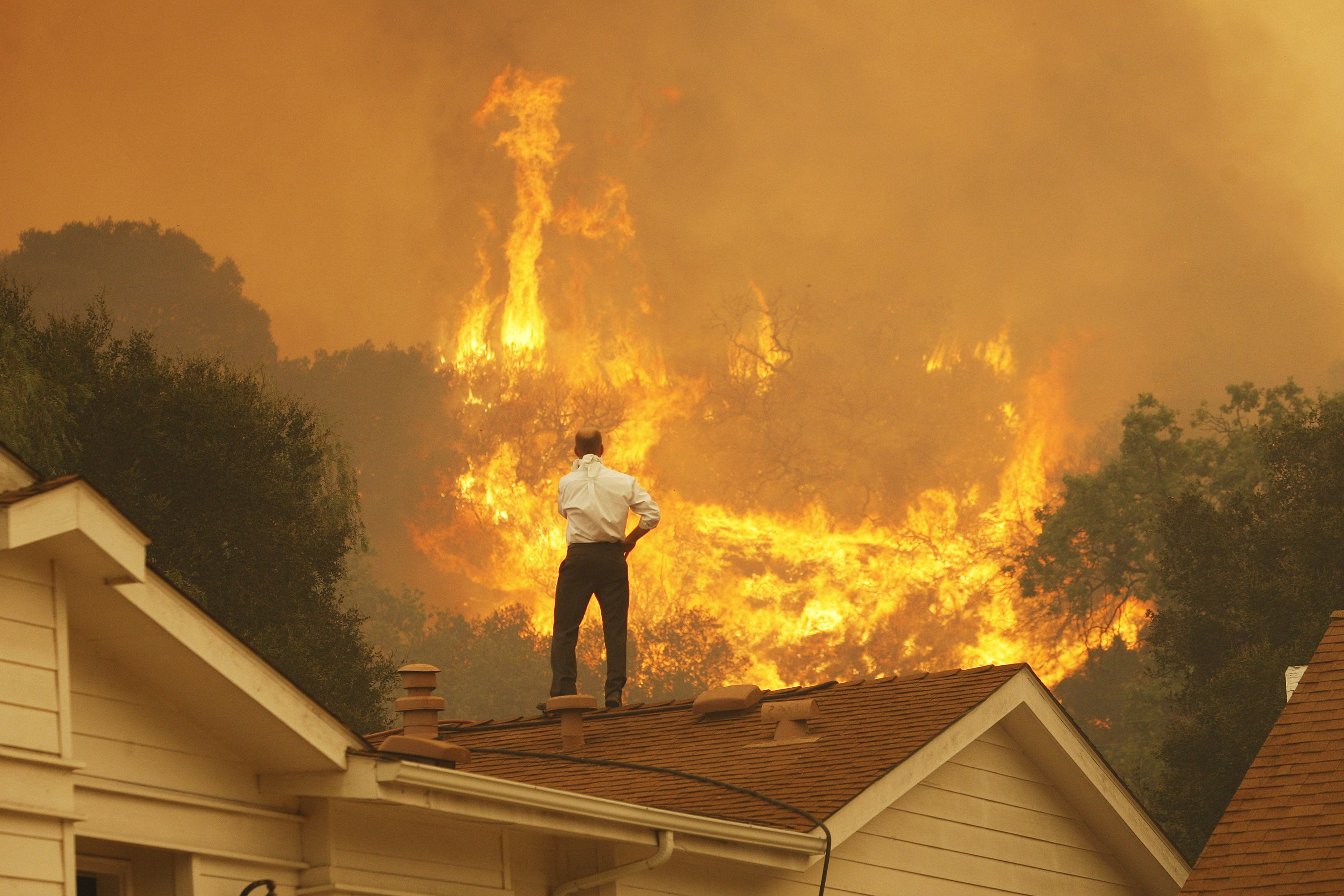 A man on a rooftop looks at an approaching wildfire, possibly linked to climate change