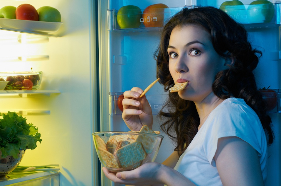 Girl opens the fridge with food
