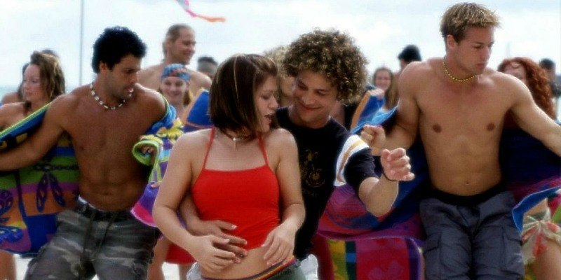 Kelly Clarkson and Justin Guarini are dancing together on a beach.