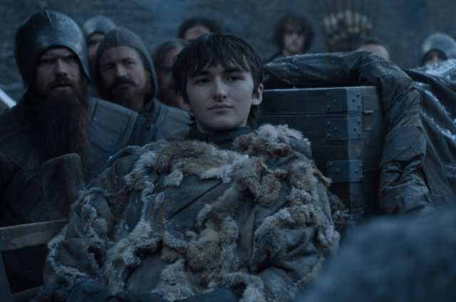 Bran sits in a fur jacket while looking at another person in front of him.