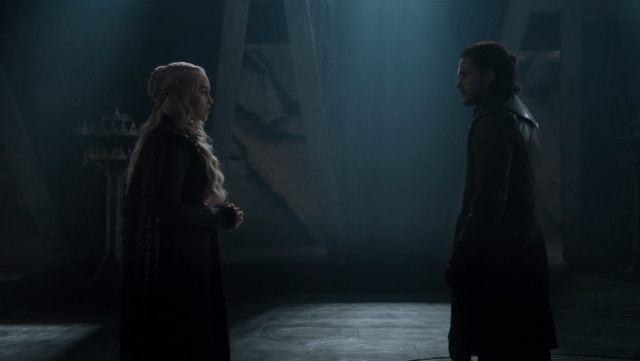 Daenerys and Jon face each other in a dark room.