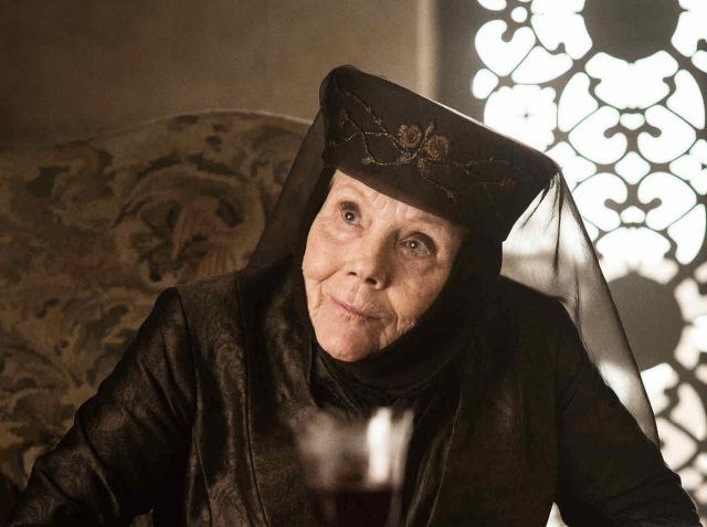 Lady Olenna looking upward with her head leaned while sitting at a table.