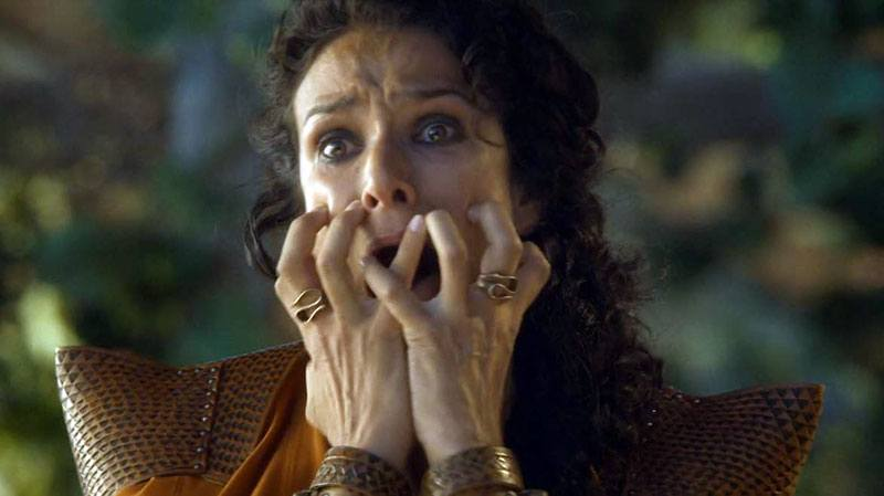 A woman clutching her mouth with her hands