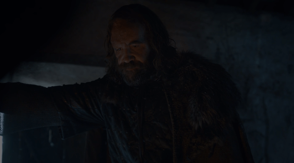 Sandor Clegane looks into the fire in a fireplace.