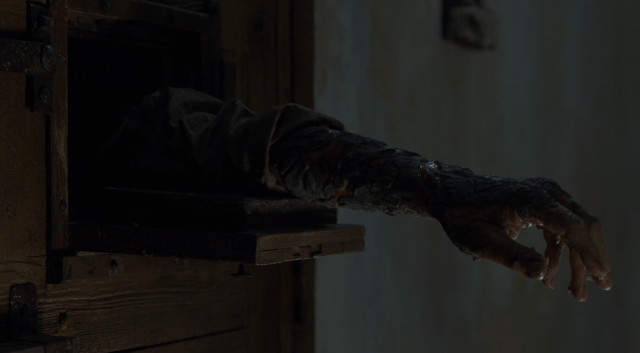 Jorah Mormont reaches an arm, covered in Greyscale, out of his cell door in a scene from the Season 7 'Game of Thrones' premiere.