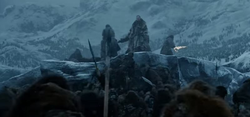 Jon Snow and two other men are on top of a hill in the snow during a battle. One is holding a sword on fire.