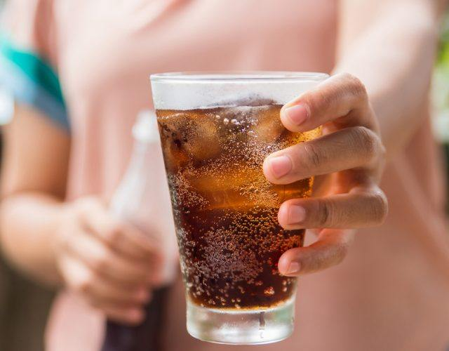 Woman hand giving glass of cola