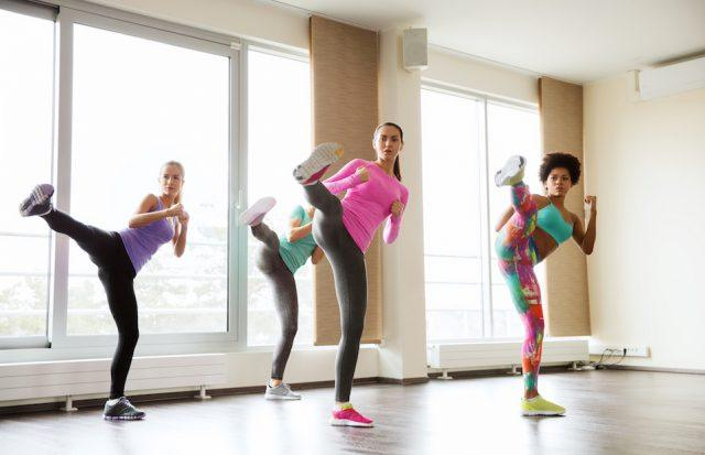 Four women do kicks at a workout class.