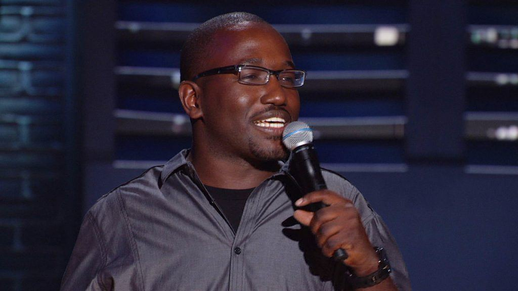 Hannibal Buress speaking into a microphone on stage