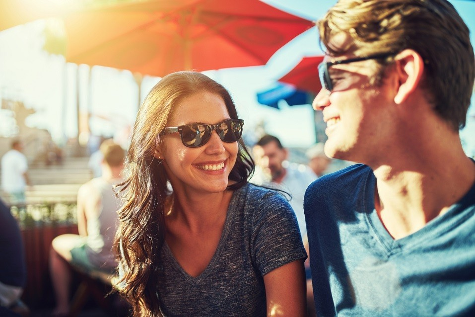 happy dating couple at outdoor restaurant with lens flare
