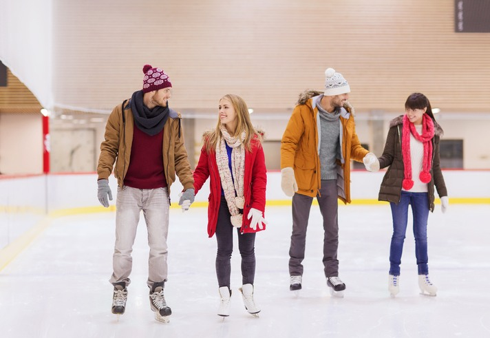 happy friends on skating rink