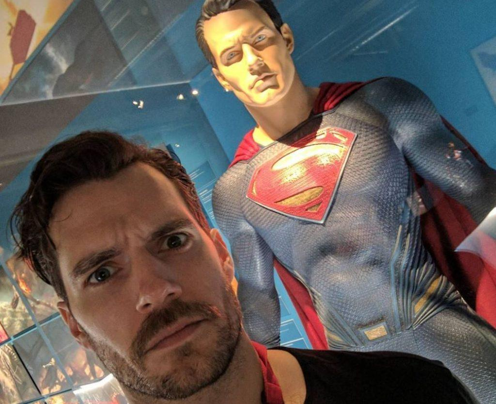 Henry Cavill standing in front of a Superman figure